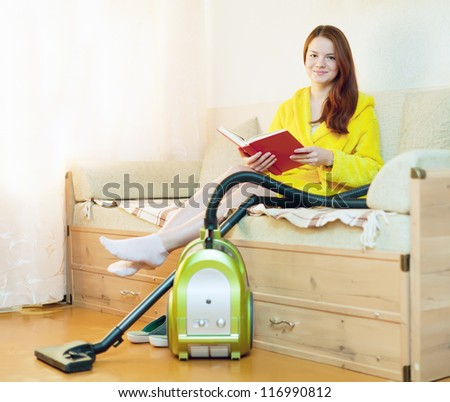 Young woman rests from household chores with book in home