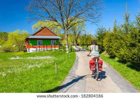 Young woman rides a bike on country road in spring time, Banica village, Beskid Niski, Poland