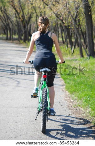 young woman riding a bicycle in a park - stock photo