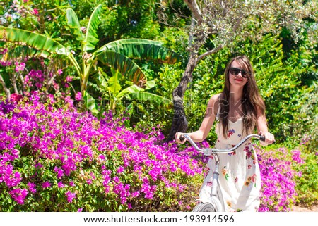 Young woman riding a bike on tropical resort at beautiful garden - stock photo