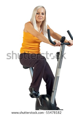 Young woman riding a fitness bicycle isolated against a white background.