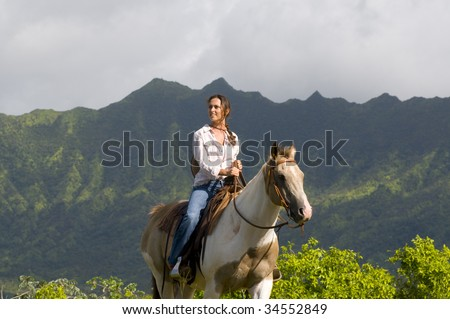 young woman riding a horse in a Kauai ranch - stock photo