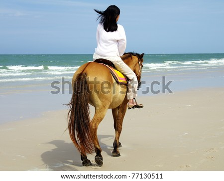 young woman riding a horse on the beach - stock photo