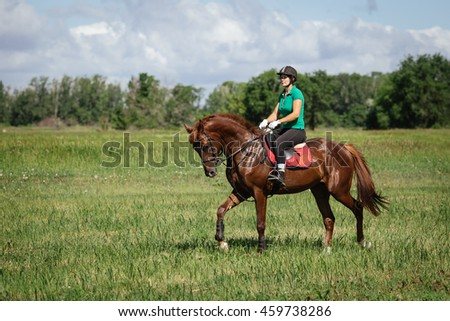 Young woman riding a horse on the green field