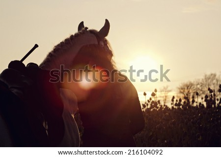 young woman riding and hug with horse at sunset