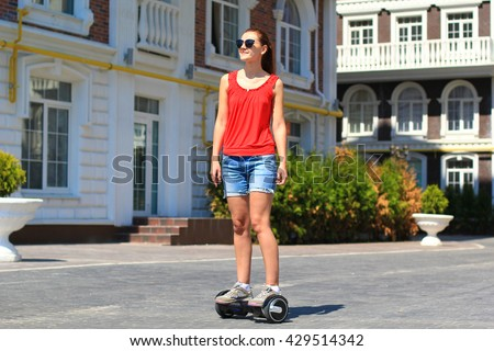 young woman riding hoverboard in the city - electrical scooter, gyro scooter, personal portable eco transport, gyroboard