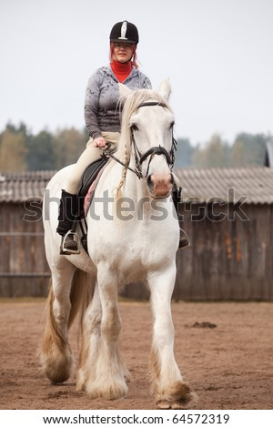 Young woman riding shire horse in arena, selected focus on horse head