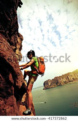 young woman rock climber climbing on seaside mountain cliff - stock photo