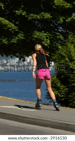 young woman rollerblading along the stanley park seawall - stock photo