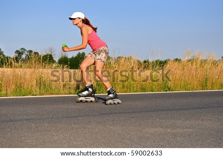 Young woman rollerskating during the sunny day. - stock photo
