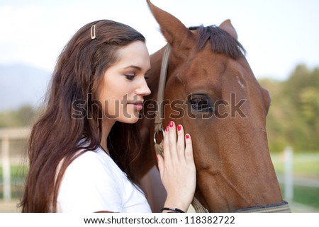 Young woman rubbing a horse - stock photo