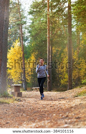 Young woman run in autumn the forest in sunset lights