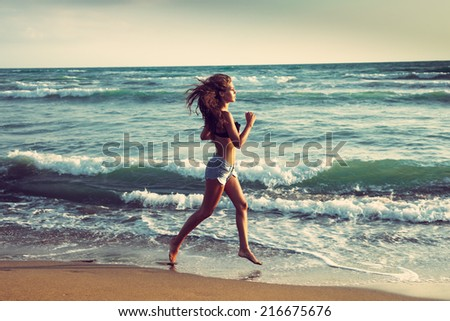 young woman run on sandy beach by the sea at sunset - stock photo