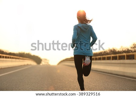 young woman runner athlete running at sunrise city road - stock photo