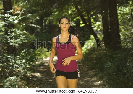 Young woman runner on forest trail