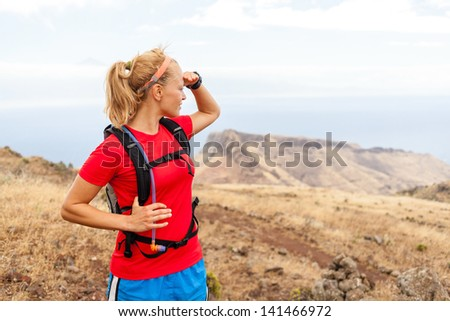 Young woman runner on trail in mountains looking at view on La Gomera island, Canary Islands. Female runner exercising outdoors in nature. - stock photo