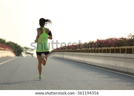 young woman runner running on city road - stock photo