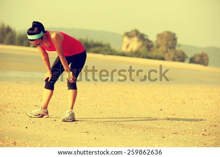 young woman runner taking a breack after running hard at beach - stock photo
