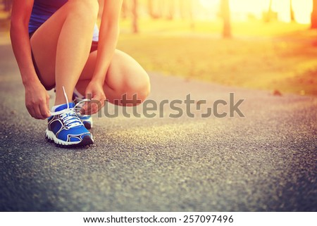 young woman runner tying shoelaces  - stock photo