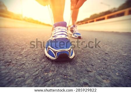 young woman runner tying shoelaces on sunrise bridge road - stock photo