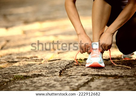 young woman runner tying shoelaces outdoor - stock photo