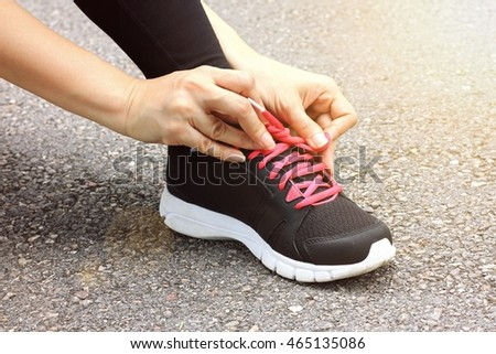 Young woman runner tying shoelaces, Running shoes close up, Aerobic sports training, New start for healthy lifestyle. (Lighting Effect Processed)