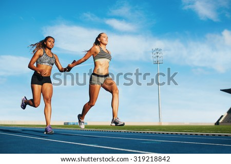 Young woman running a relay race and giving relay baton to her teammate. Female runner passing the relay baton during race. - stock photo