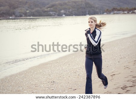 Young Woman running along the beach - stock photo