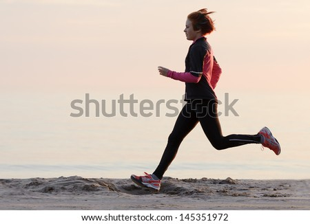 Young woman running along the waterfront - stock photo