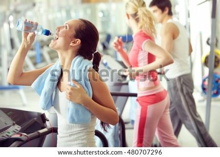 Young woman running and drinking water with people on background