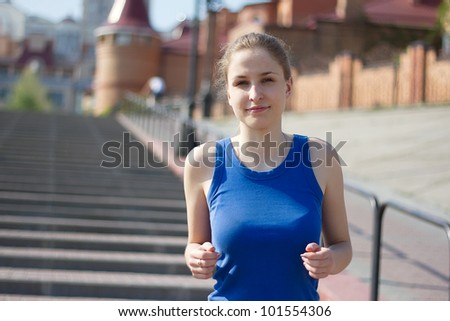 Young woman running and training in city streets - stock photo