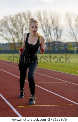 Young woman running at a track and field stadium - stock photo