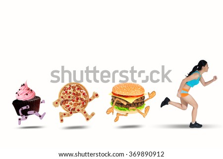 Young woman running away from junk food while wearing sportswear, isolated on white background