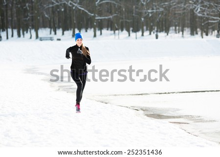 Young woman running during winter at park - stock photo