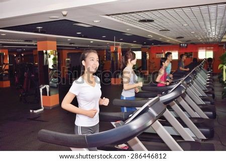 Young woman running in a fitness club - stock photo