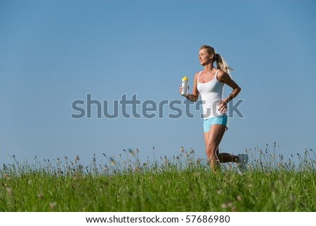 Young woman running in a meadow under a blue sky