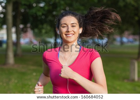 Young woman running in a park listening to music - stock photo