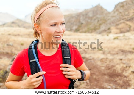 Young woman running in mountains on summer sunny day. Female runner exercising outdoors in nature, sunset, La Gomera, Canary Islands. - stock photo