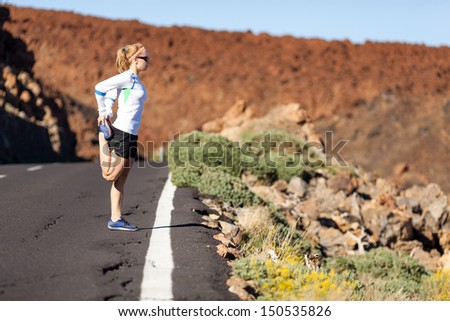 Young woman running in mountains on  sunny day. Female runner exercising and stretching outdoors in nature, sunset. - stock photo