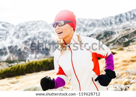 Young woman running in mountains on winter fall sunny day. Female cross-country runner exercising outdoors in nature, sunset.