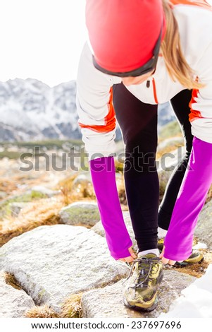 Young woman running in mountains on winter fall sunny day. Female runner tying sports shoe. Motivation and inspiration concept fitness exercising outdoors adventure. - stock photo