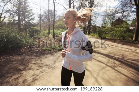Young woman running in park in sunshine on beautiful summer day. Fitness model training outdoor for good health. - stock photo