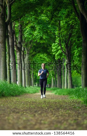 Young woman running in the green forest - stock photo