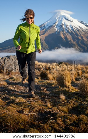 Young woman running in the mountains - stock photo
