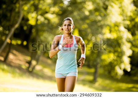 Young woman running in the park - stock photo