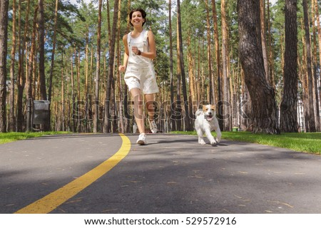 Methods to Impress a Sagittarius Female stock photo young woman running in the park with her dog 529572916
