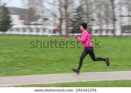 Young woman running on a cold winter day in an urban park with a panning effect. - stock photo