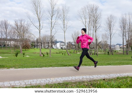 Young woman running on a cold winter day on an urban park. Profile or side view.