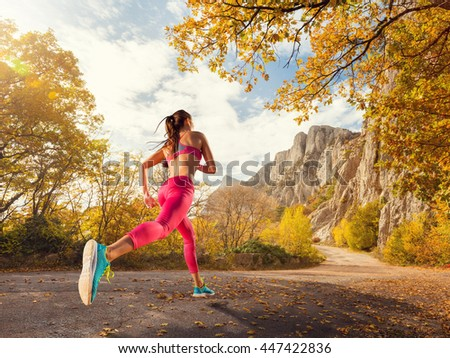 Young woman running on a mountain road in the beautiful nature. Girl runner in sneakers jogging workout outdoors. Weight loss concept. Healthy lifestyle. - stock photo
