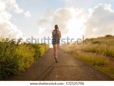 Young woman running on a rural road during sunset - stock photo